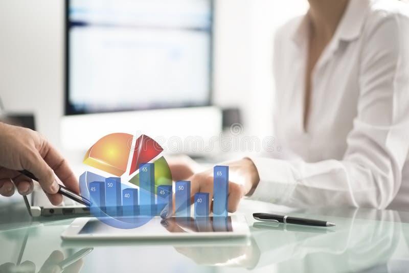 Sócios comerciais ou colegas de escritório que analisam gráficos e carta de negócio no escritório imagem de stock royalty free
