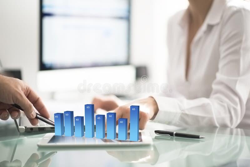 Sócios comerciais ou colegas de escritório que analisam gráficos e carta de negócio no escritório fotos de stock royalty free