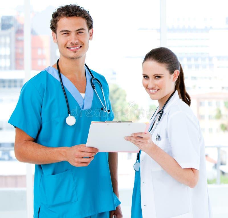 Sócios de sorriso que prendem um diagnóstico paciente imagem de stock