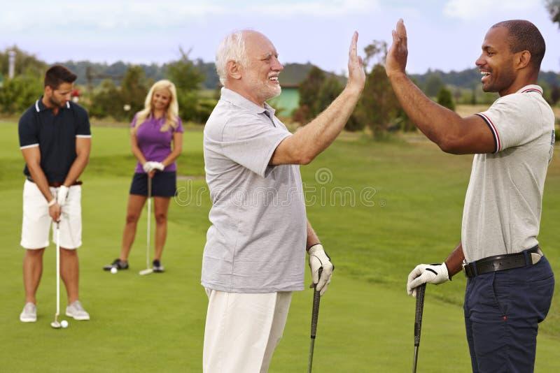 Sócios do golfe que comemoram o bom tiro foto de stock royalty free