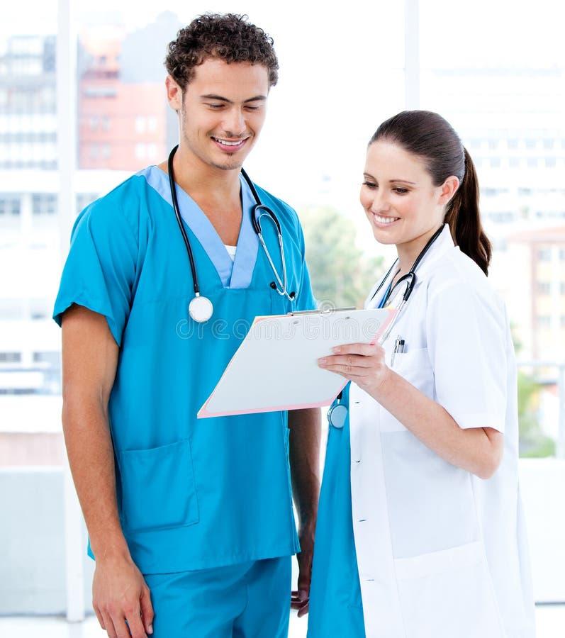 Sócios médicos felizes que olham o diagnóstico fotos de stock royalty free