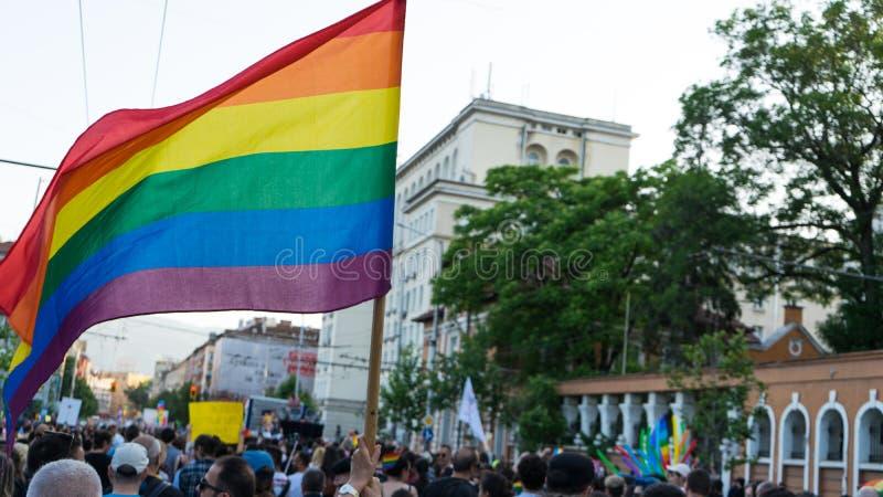 Sófia/Bulgária - 10 de junho de 2019: Os suportes acenam bandeiras dos arcos-íris ao lado de Pride Parade anual imagem de stock