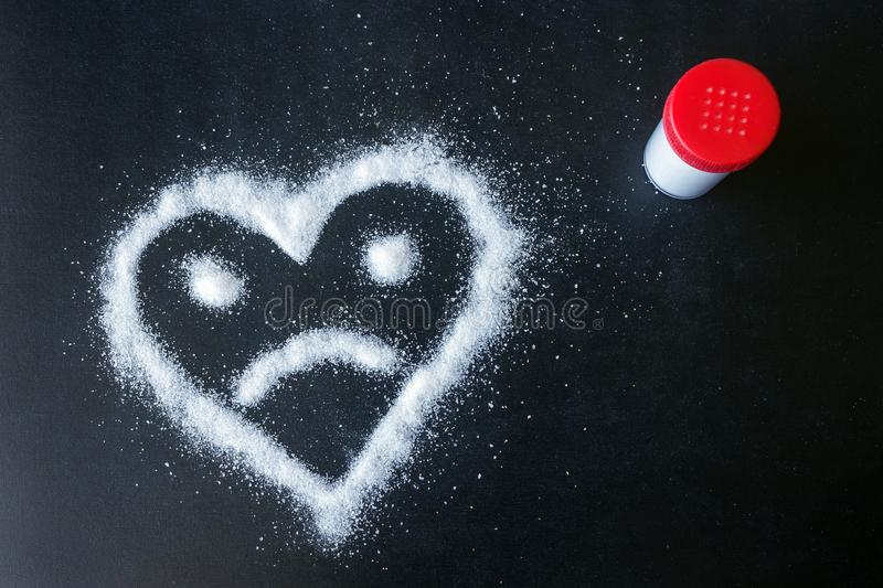 Sól rozpraszająca na czerni powierzchni Patroszony serce z smutną twarzą fotografia stock