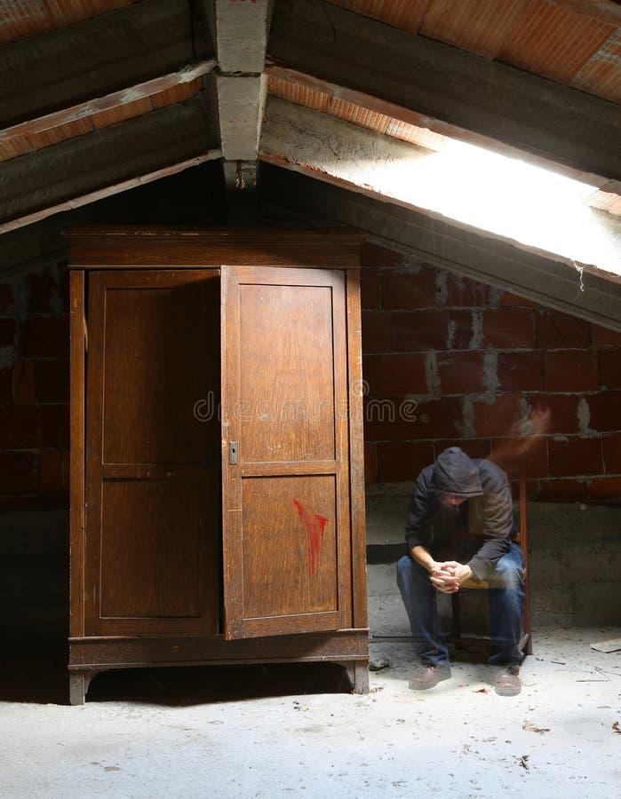 sótão com um vestuário velho e a presença de um fantasma que senta o imagens de stock