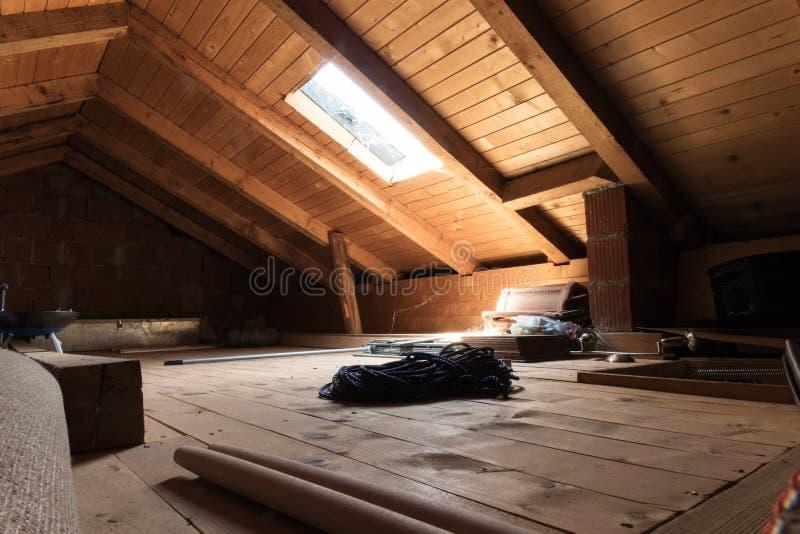 Sótão de madeira abandonado com a janela diagonal do telhado imagens de stock royalty free