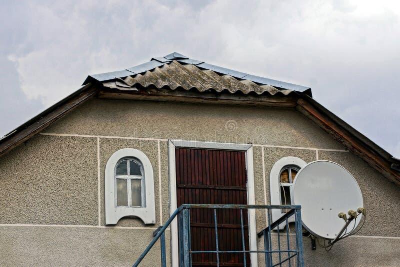 Sótão de uma casa rural cinzenta com uma porta com janelas e uma antena parabólica no fundo do céu foto de stock