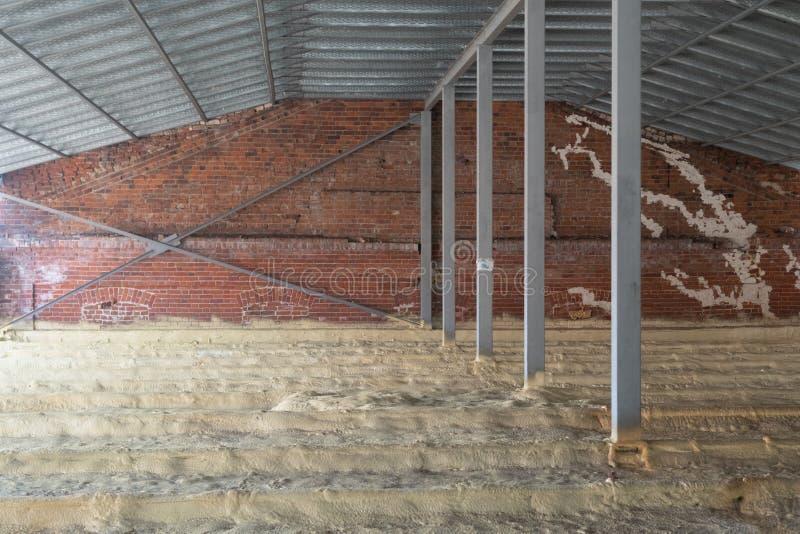 Sótão de uma casa sob a construção com isolação no assoalho tubula??es Parede de tijolo foto de stock royalty free
