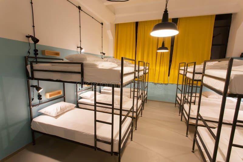 Sótão moderno com as camas de beliche na pousada da juventude com salas do dormitório foto de stock royalty free
