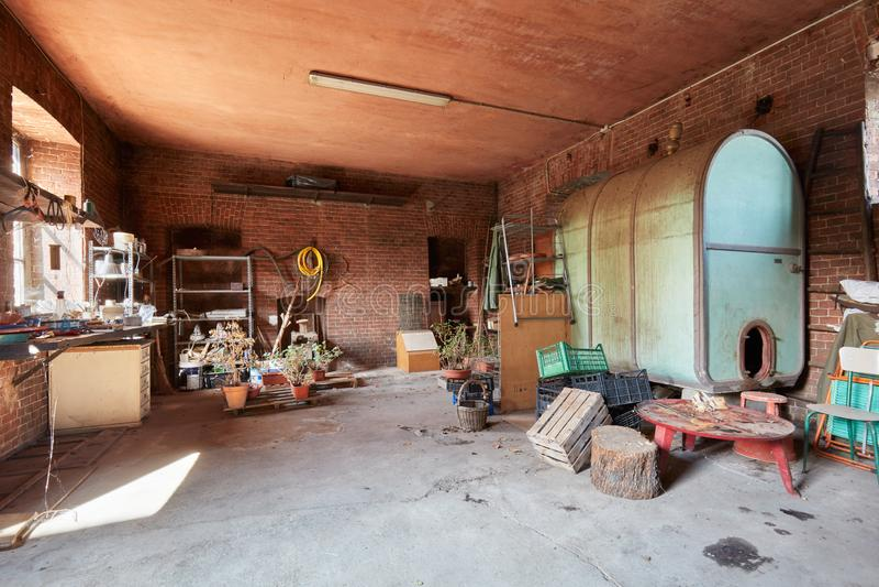S?tano sucio con las paredes del barril grande y de ladrillos rojos en casa vieja foto de archivo