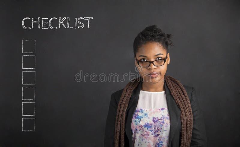 Södra - afrikan eller afrikansk amerikankvinnalärare eller student med en kontrollista på bakgrund för kritasvartbräde fotografering för bildbyråer