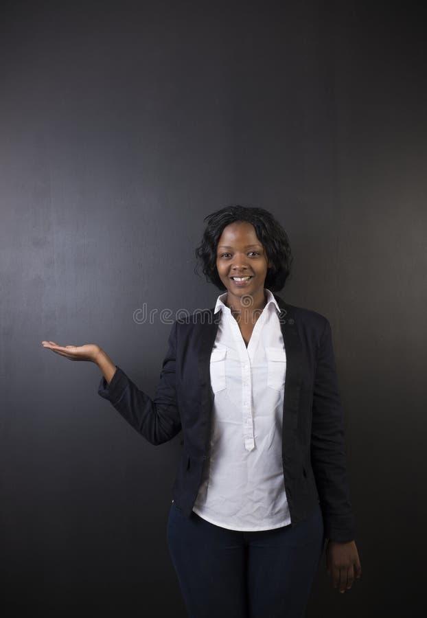 Södra - afrikan eller afrikansk amerikankvinnalärare på svart bräde arkivfoto