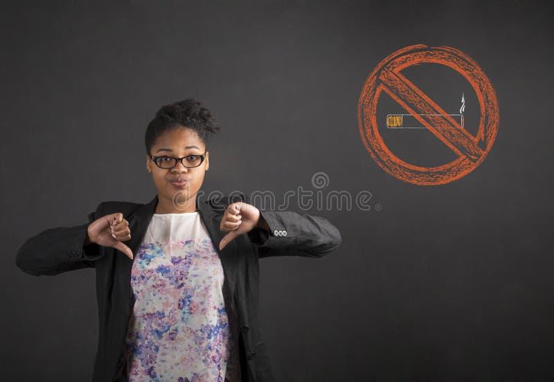 Södra - afrikan eller afrikansk amerikansvart kvinnalärare eller student med för tummar handsignalen ner till inget - röka på ett royaltyfria foton