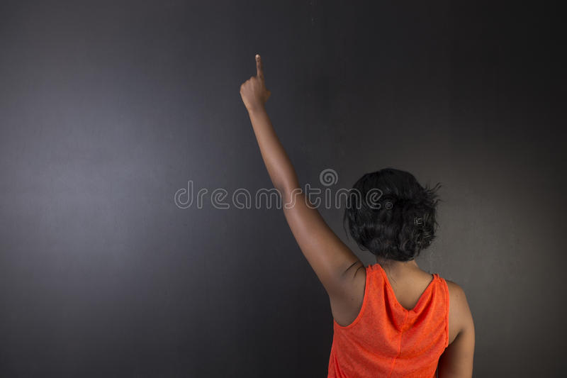 Södra - afrikan eller hand för afrikansk amerikankvinnalärare upp på kritasvartbräde arkivfoto