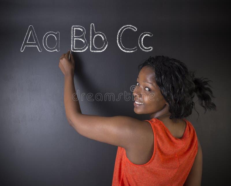 Södra - afrikanen eller den afrikansk amerikankvinnaläraren eller studenten lär att alfabetet skriver handstil royaltyfri bild