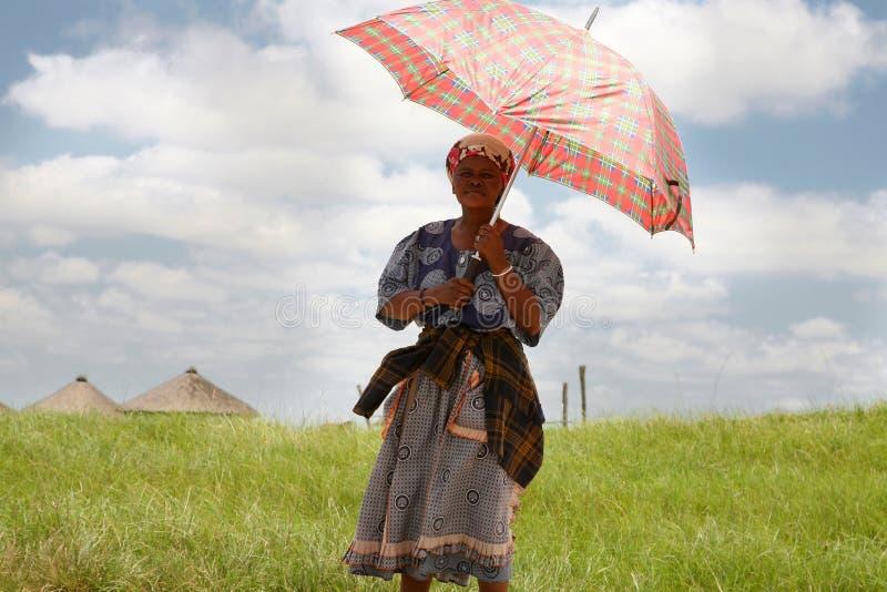 Södra - afrikansk kvinna som rymmer ett paraply för att skydda henne från royaltyfri bild