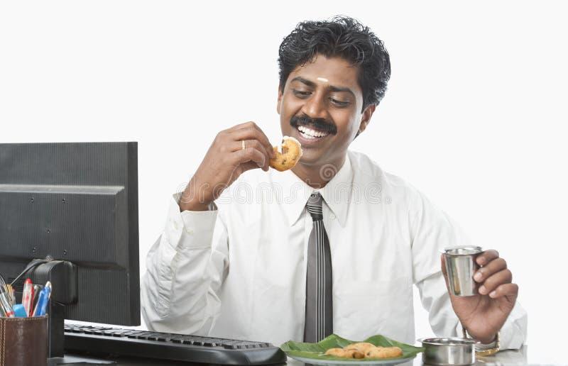 Södra indisk affärsman som arbetar i ett kontor och har mat arkivfoton