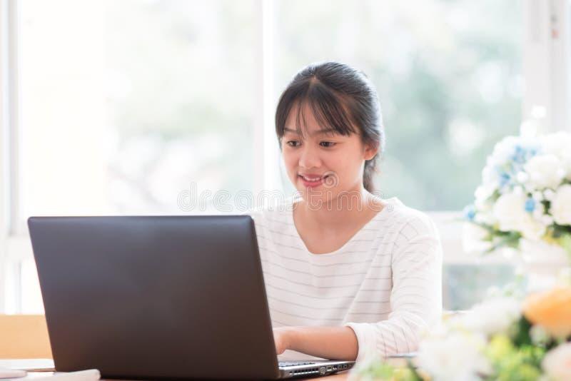 Sök efter sociala nätverk online med Smartphone Concept: Asian Cute Woman använder en svart bärbar dator för att handla eller skr royaltyfri bild