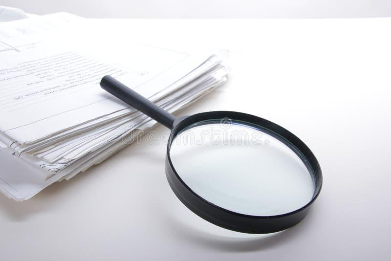 Sök med förstoringsglaset som söker efter information i böcker, ritningar, tidskrifter Revisionskontroll Kopieringsutrymmetext royaltyfria foton