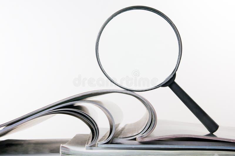 Sök med förstoringsglaset som söker efter information i böcker, ritningar, tidskrifter Revisionskontroll Kopieringsutrymmetext royaltyfria bilder