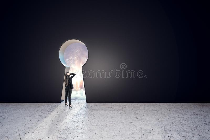 Söka efter ett lösningskoncept med en affärskvinna som söker efter nyckelhål i den stora svarta väggen royaltyfri bild