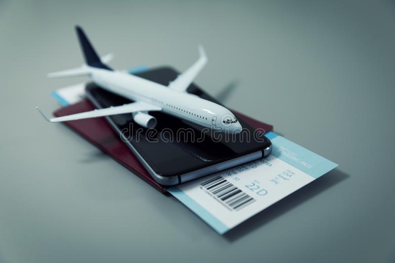 Söka köpande och boka flyg som är online- med smartphonen fotografering för bildbyråer