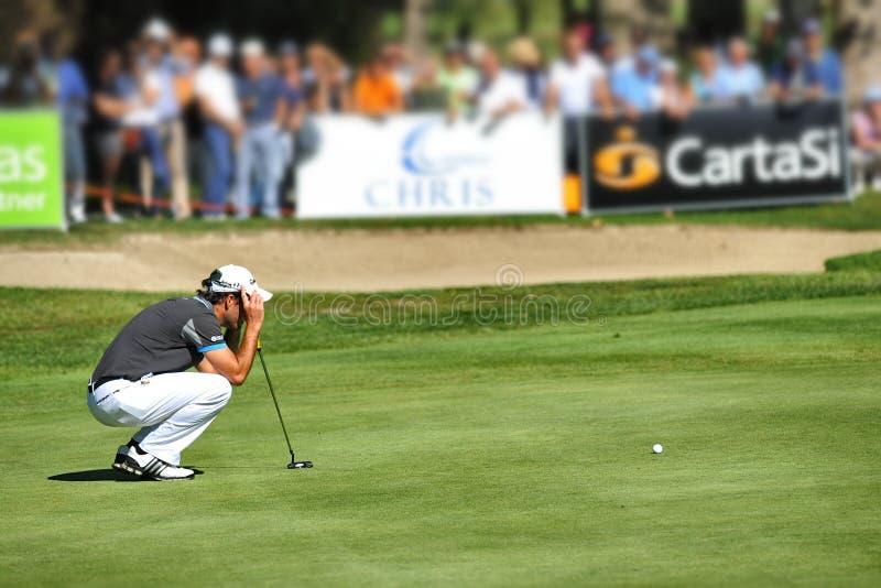 Sökande för koncentrat för Turin Italien okänt golfspelare som linjen squatted på gräsplan arkivbild