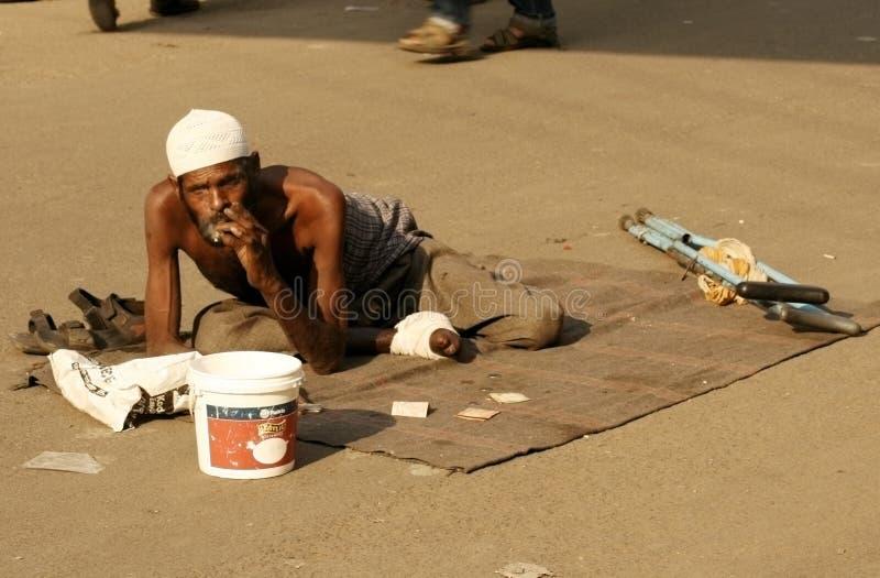 Sökande hjälp för indisk sjuk tiggare på en upptagen väg royaltyfri fotografi
