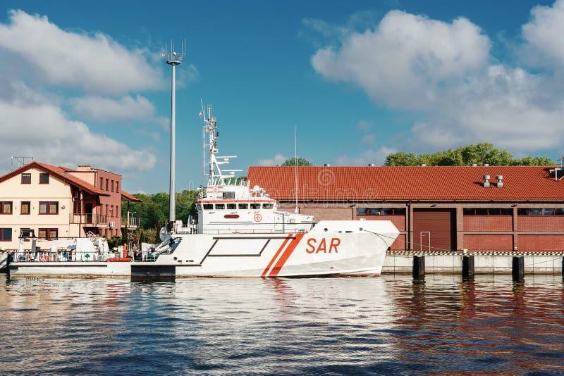 S?kande- och r?ddningsaktionfartyg som f?rt?jas p? hytten Vitt fartyg med r?d liine p? skrov royaltyfria foton