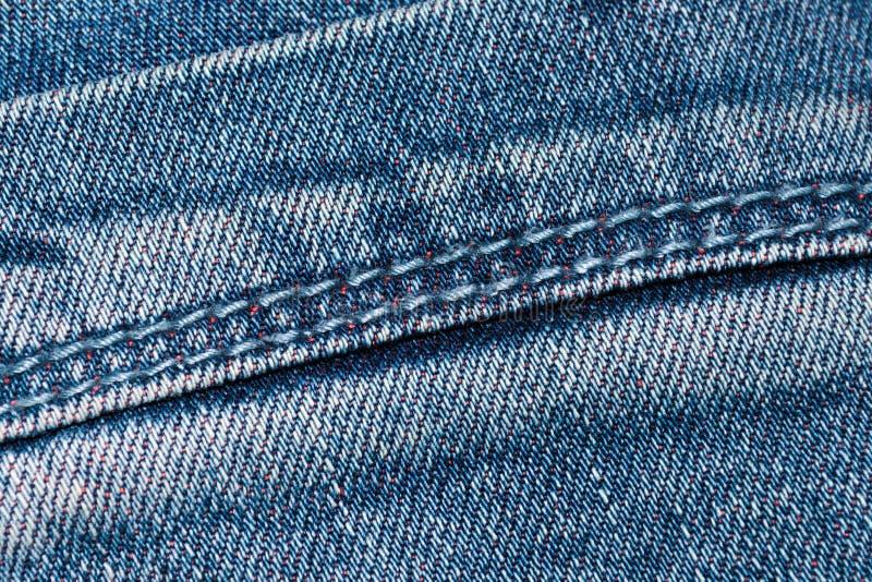Söm på blått grov bomullstvilltyg arkivbild