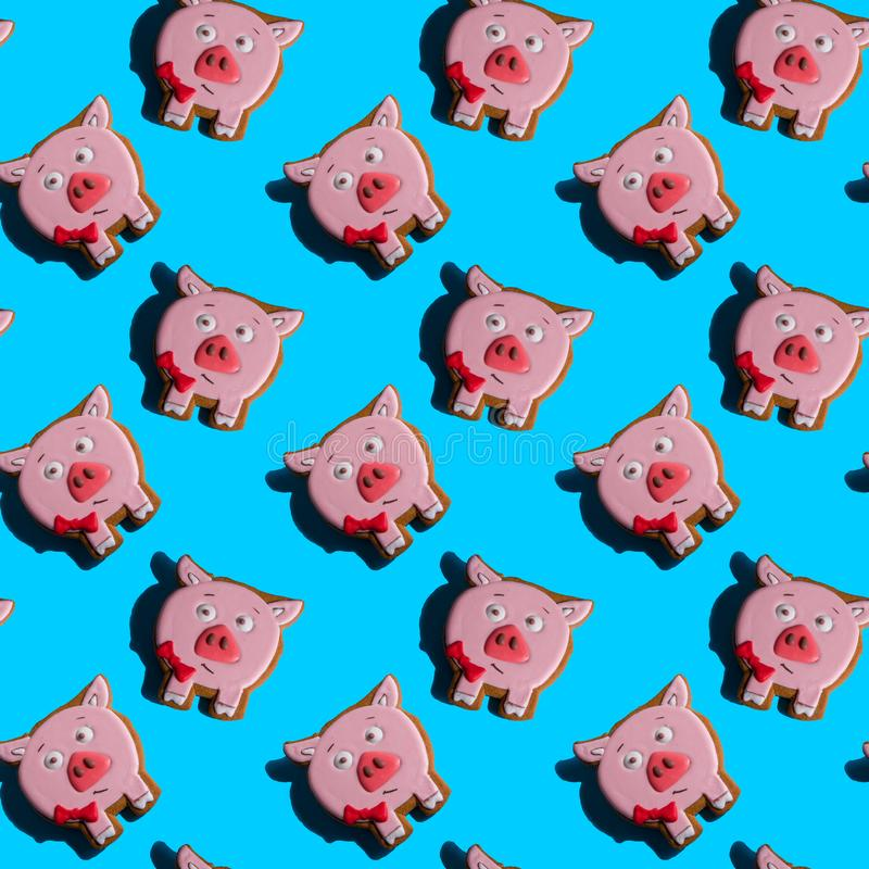 Sömlös bakgrund med pepparkakan i form av svin på en livlig blå bakgrund Hårda skuggor Julbackgroun för abstrakt konst royaltyfri fotografi