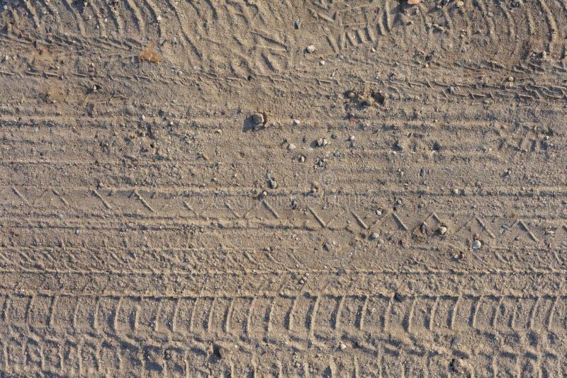 Sömlös grusvägtexturbakgrund Spår av bilar på sanen royaltyfri bild