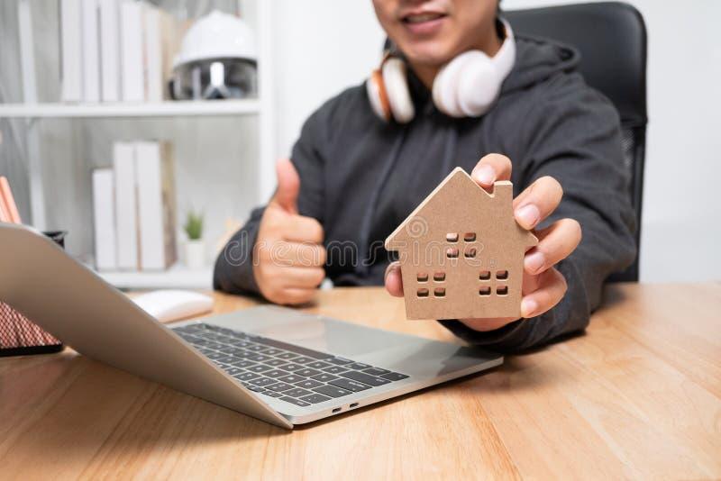 Sömmande affärsman som har ett trähus i hemmet Begreppet arbete från hemmet till slutet av Coronavirus COVID royaltyfri bild