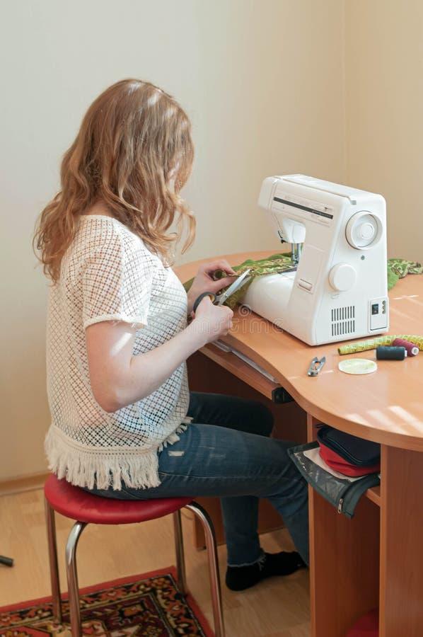 Sömmerska med blont hår i den vita t-skjortan som sitter på blå stol nära trätabellen med symaskinen som klipper tyg royaltyfri foto