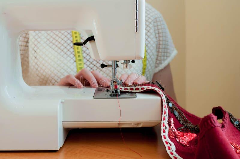 Sömmerska som sitter på symaskinen och arbetar, i att sy studion arkivfoton