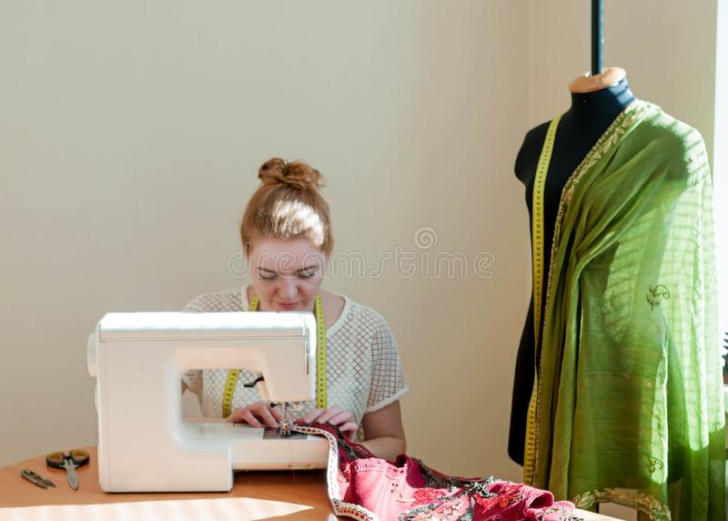 Sömmerska som sitter på symaskinen, skyltdocka och arbetar i studio royaltyfri foto