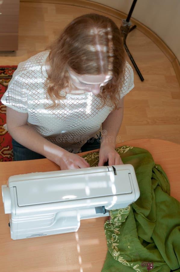 Sömmerska som sitter på trätabellen med symaskinen, torkduken och att arbeta arkivbild