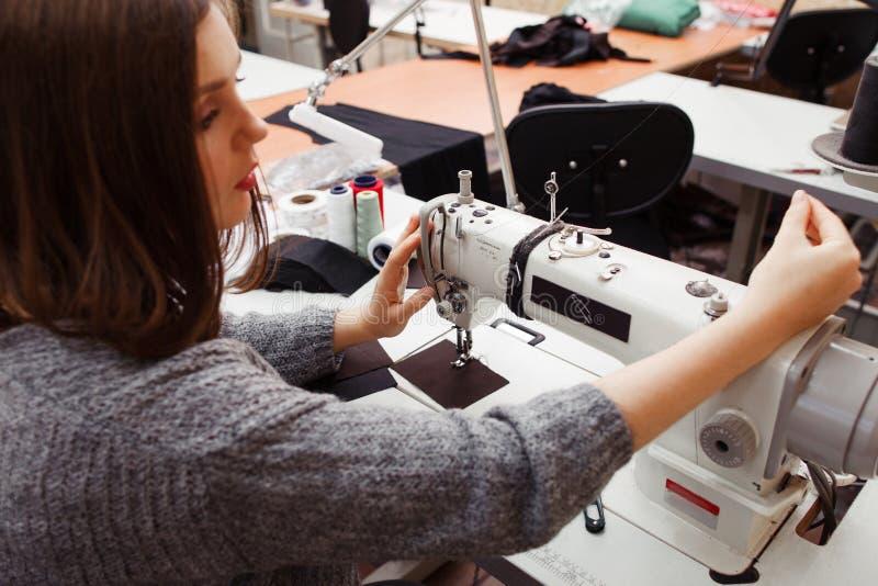 Sömmerska som trimmar symaskinen för arbete arkivfoton