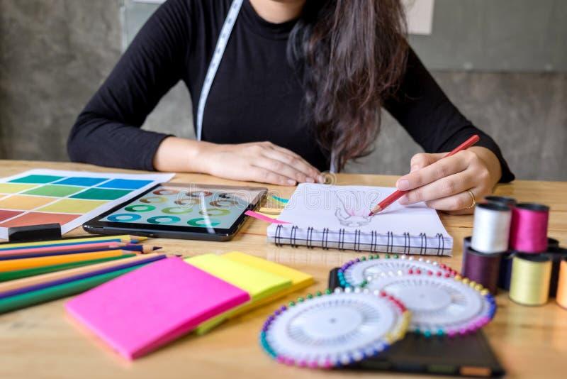 Sömmerskan eller formgivaren för ung kvinna som arbetar som modeformgivare och drar, skissar för kläder och väljer färgstången i  arkivfoto