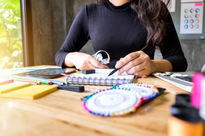 Sömmerskan eller formgivaren för ung kvinna som arbetar som modeformgivare och drar, skissar för kläder yrke och jobbockupation, arkivfoton