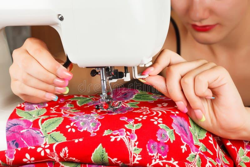 Sömmerskan syr tyg på symaskinen royaltyfri foto