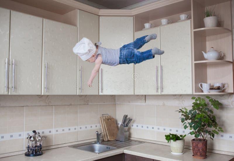 sömn av barnet tillväxt under sömn som en attraktiv unge i köket flyger Svävningeffekt läcker matkock i en vit royaltyfri fotografi