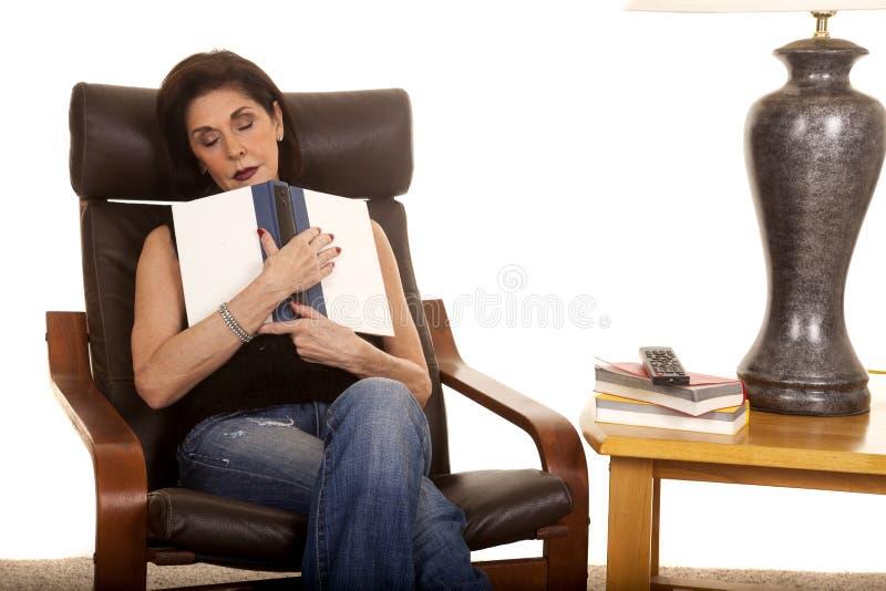 Sömn för äldre kvinna med boken i stol fotografering för bildbyråer