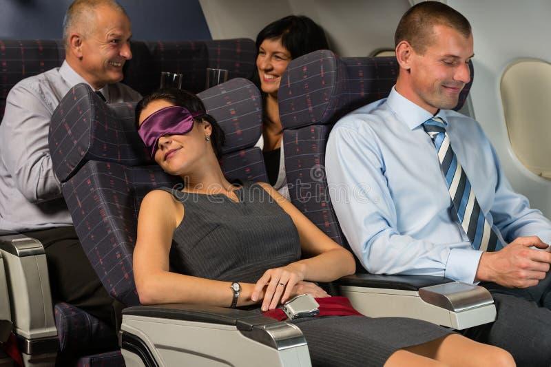 Sömn för affärskvinna under flygflygplankabinen royaltyfri foto