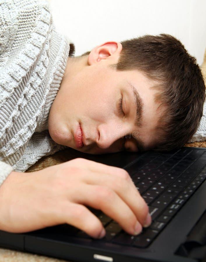 Sömn för ung man på bärbara datorn arkivfoton