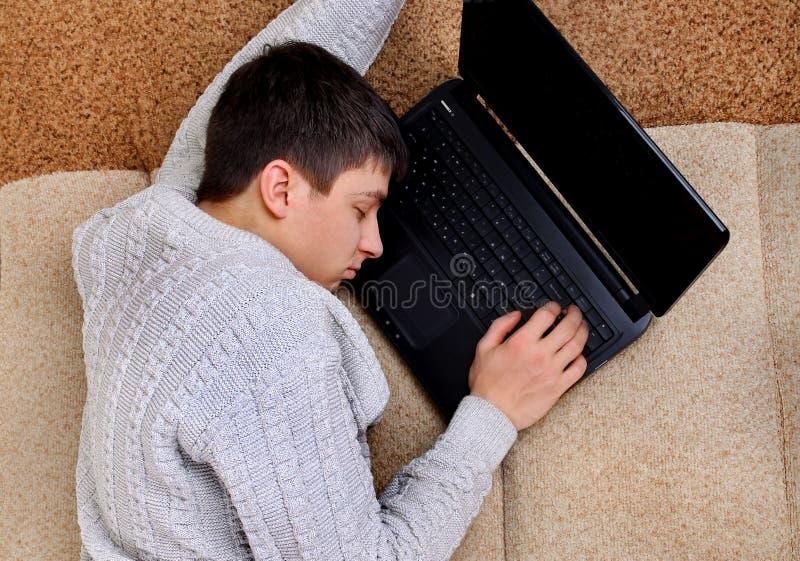 Sömn för ung man på bärbara datorn royaltyfria foton