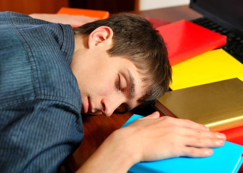 Sömn för ung man på böckerna arkivfoton