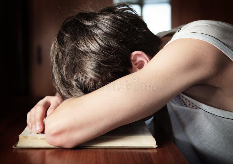 Sömn för ung man på tabellen royaltyfria bilder