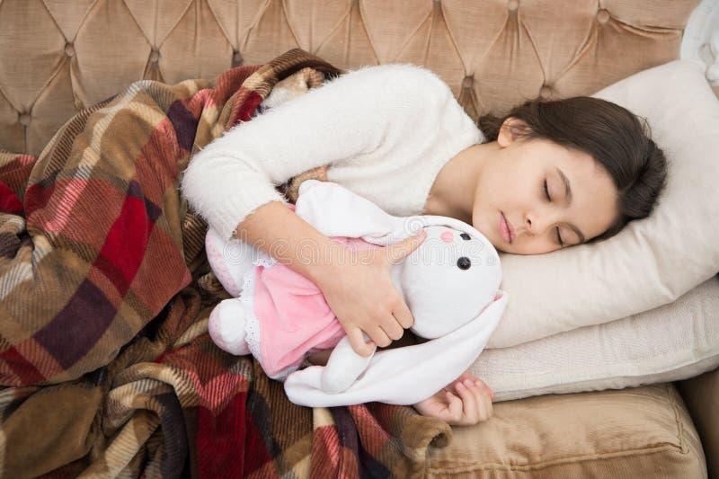 Sömn med leksaken Flickan tycker om aftontid med den favorit- leksaken Ungen lägger bakgrund för filten för kudden för soffan för arkivfoton