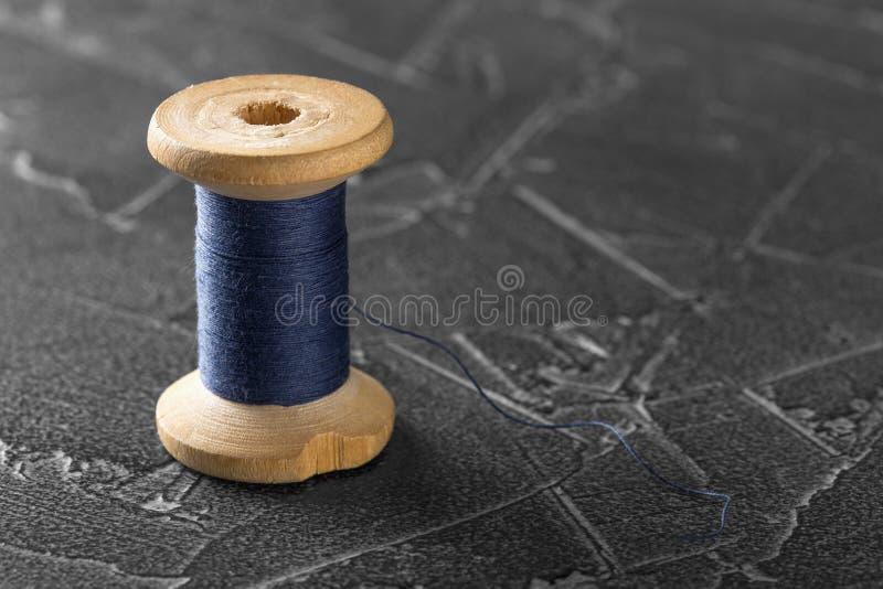 Sömnadtråd på en gammal trärulle med mörkerbetongbakgrund royaltyfria foton