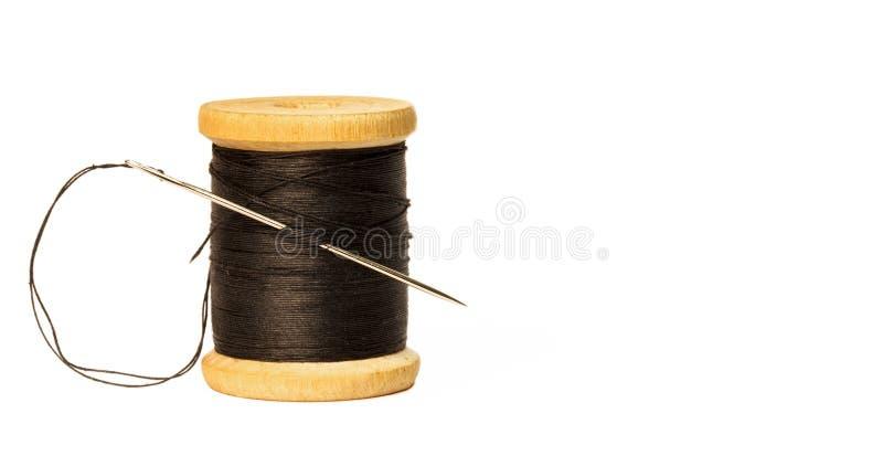 Sömnadvisaren med den svarta tråden som klibbas i trärulle med svart, dragar tätt upp isolerat på vit arkivbild